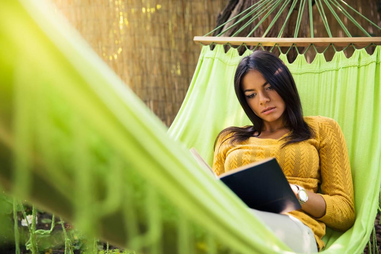 Woman reading bible on hammok